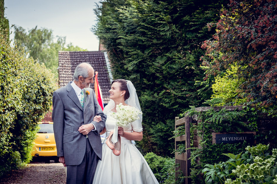bride and father looking at each other outside the family home