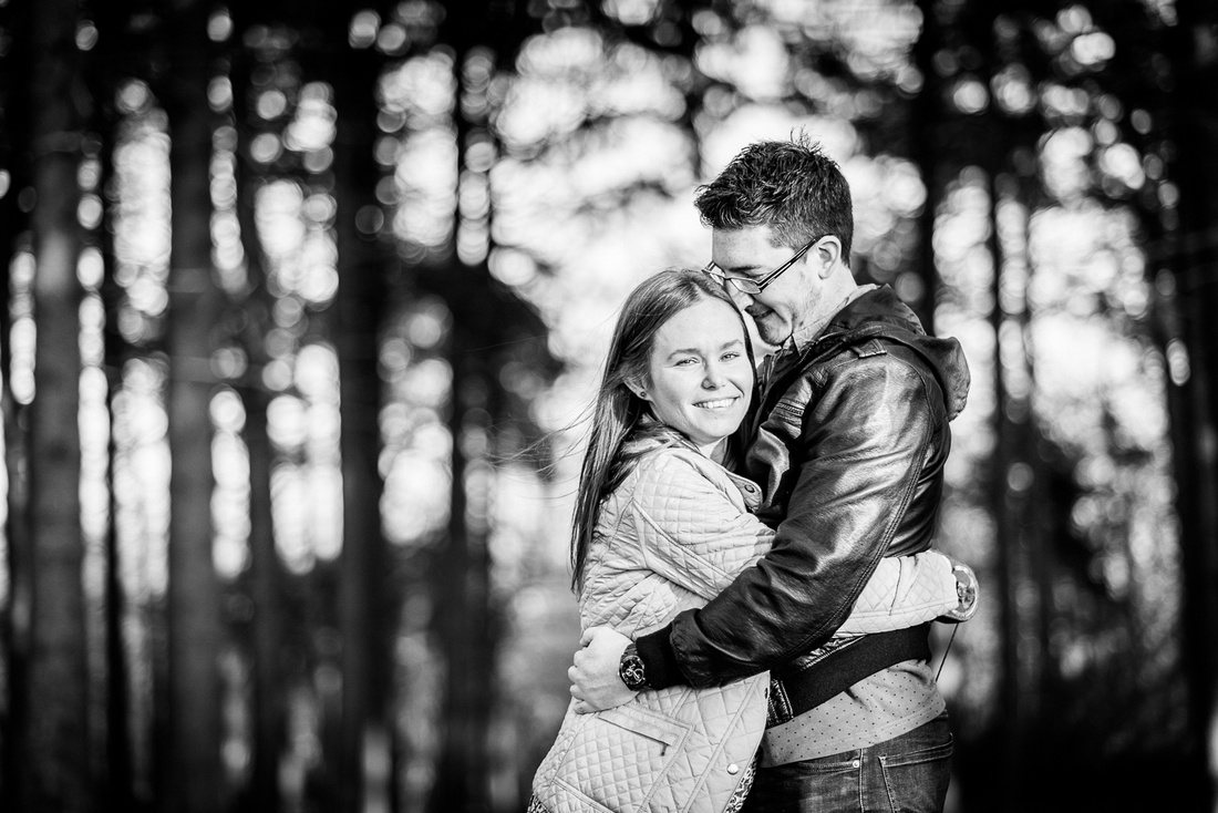 engaged couple cuddle in the Lickey Hills
