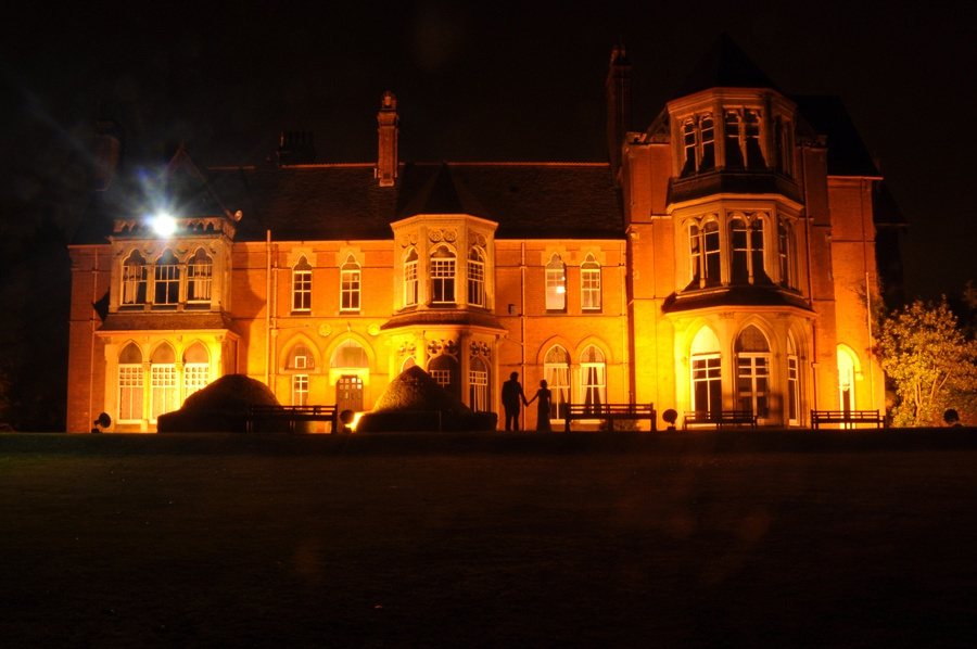 Wedding photography at Highbury Hall in Birmingham lit up at night bride groom silhouette portrait