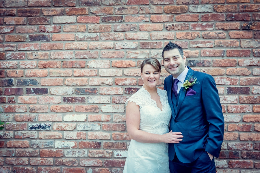 Wedding Photography at Curradine Barns in Worcestershire  bride groom relaxed portrait brick wall