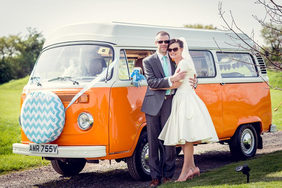 bride and groom in sunglasses with orange vintage VW Camper Van