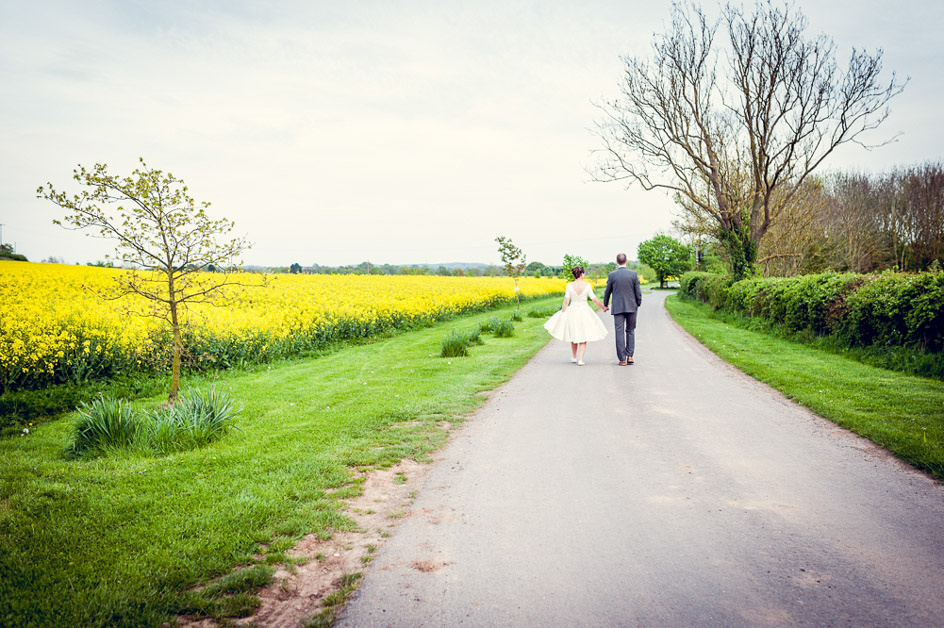 bride and groom portrait walk past oil seed rape field