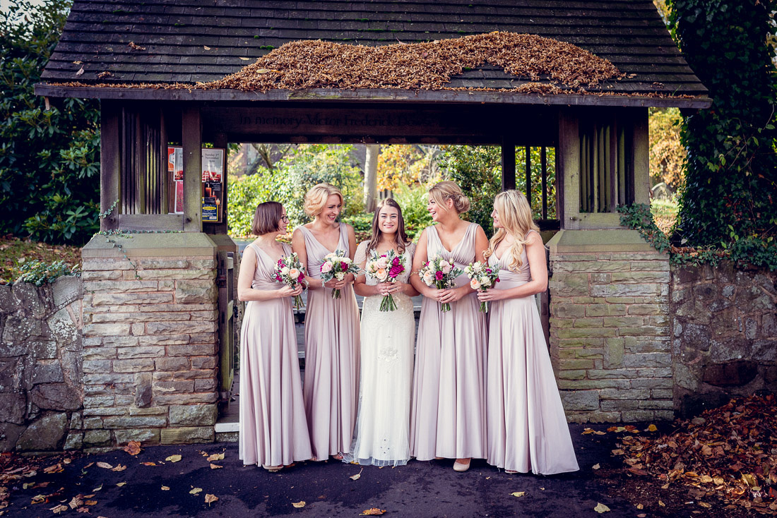 bride and bridesmaids laughing outside Hampton in Arden Church
