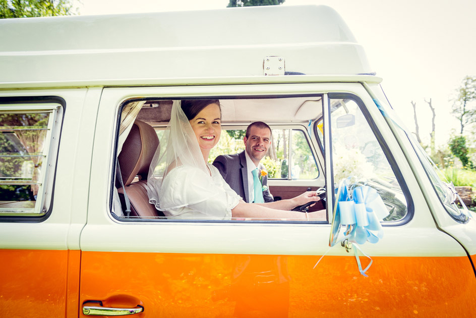bride and groom drive off in vintage camper van