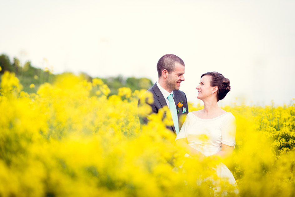 romantic bride and groom portrait in oil seed rape field