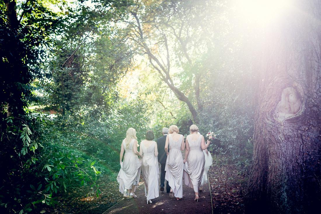 bride walking to church through trees in Autumn sunshine