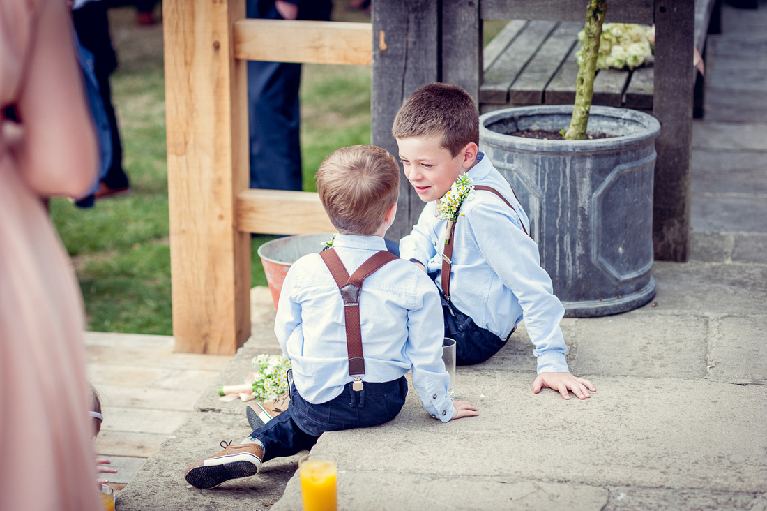 page boys in braces relax at Cripps Barn wedding