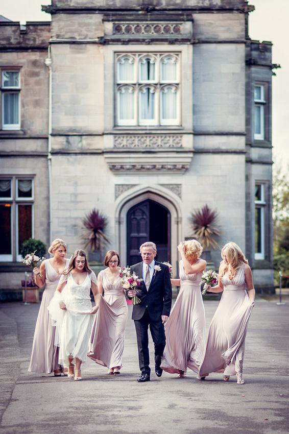 bride walking to wedding with dad and bridesmaids at Hampton Manor