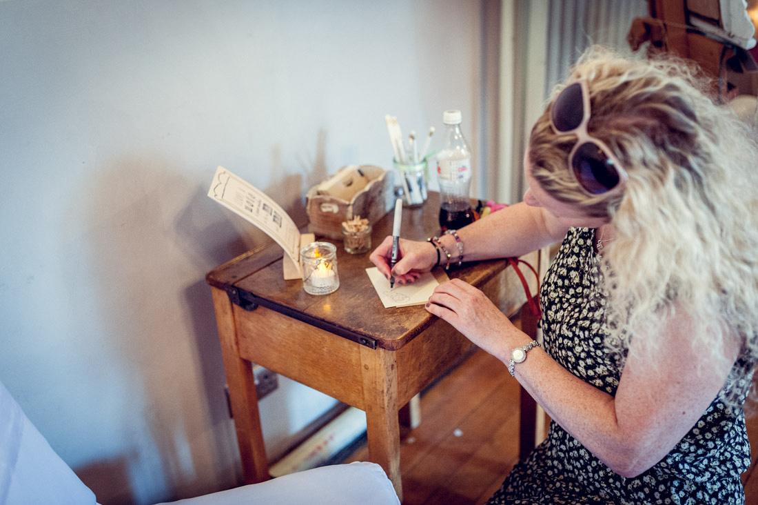 guest writing postcard on vintage school desk at Warwickshire wedding