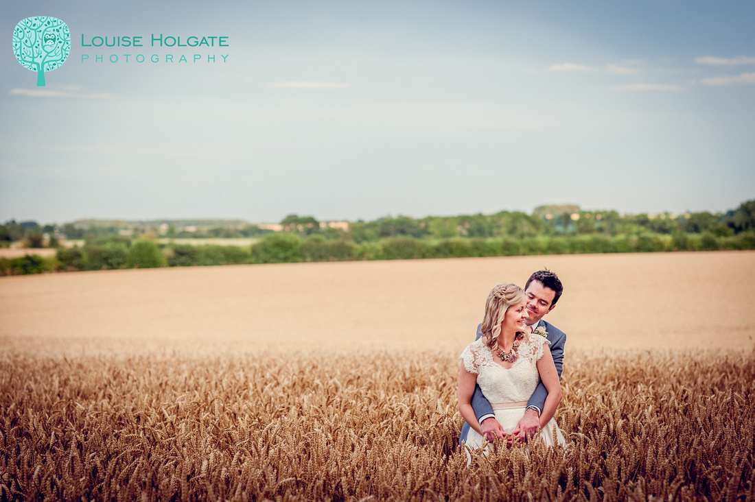 bride and groom in cornfield at Cripps Barn in the Cotswolds