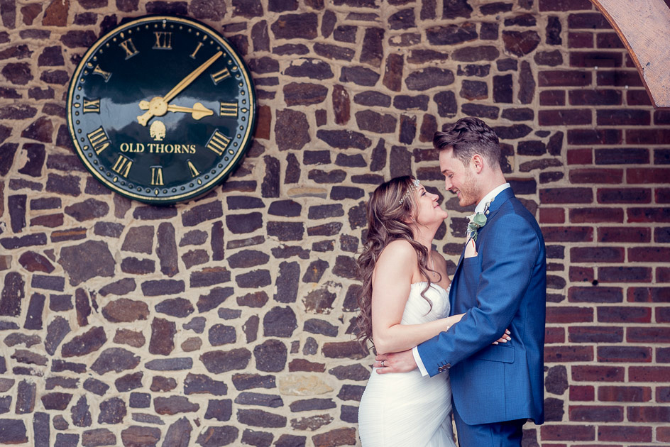 bride and groom looking at each other by clock at Old Thorns wedding venue