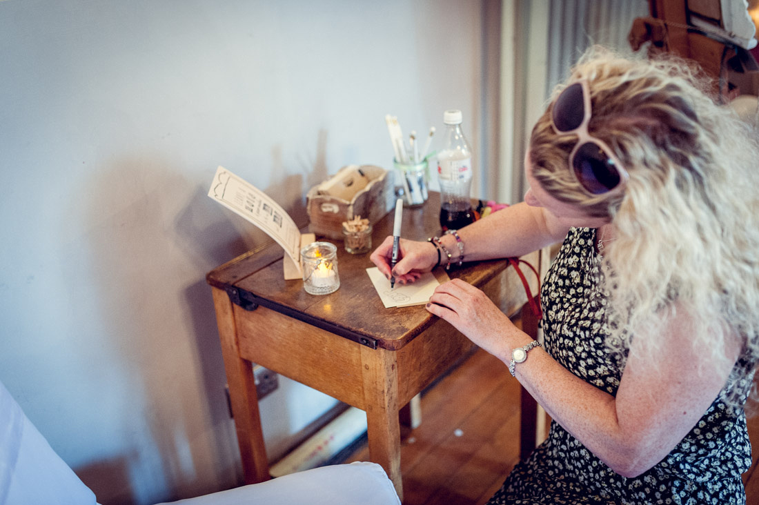 guest writing postcard on vintage school desk at Warwickshire wedding