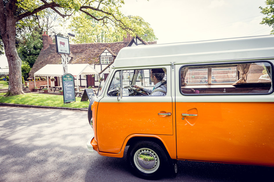 groom arrives in vintage orange VW camper van
