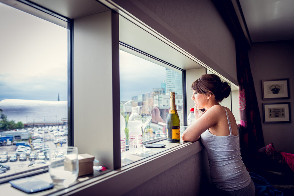 bridesmaid looks out over Birmingham during wedding preparations
