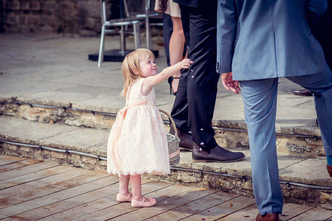 flowergirl throws confetti at groom