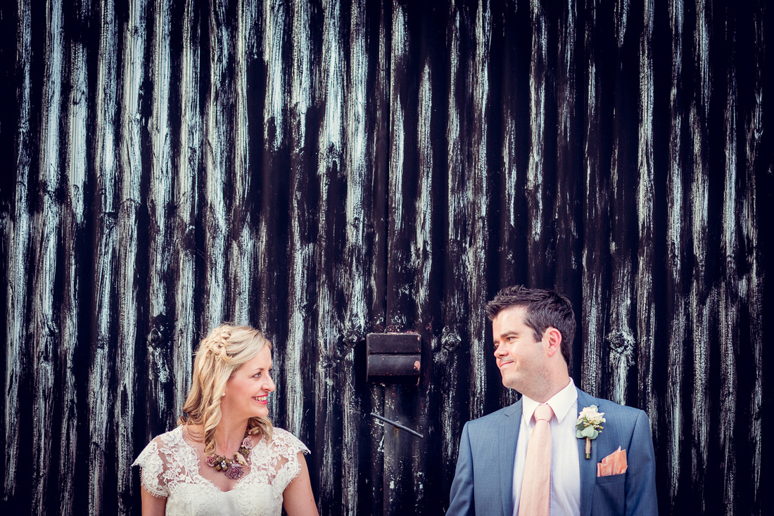 bride and groom portrait in front of metal doors at Cripps Barn wedding