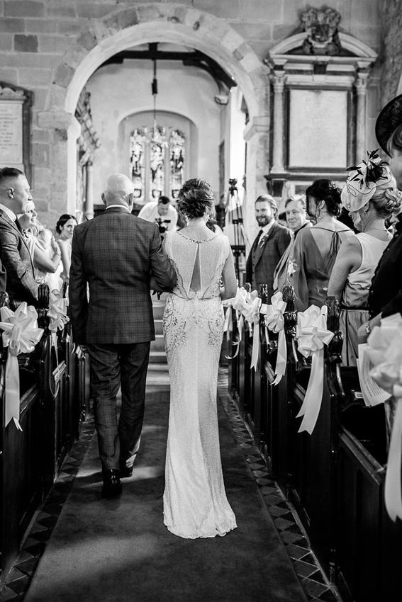 bride walking down aisle of St Leonard's Church Beoley