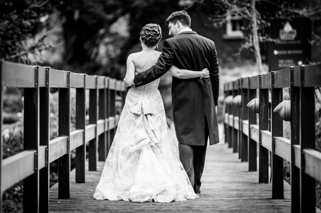 bride and groom walk across bridge at Ardencote Manor in Warwickshire