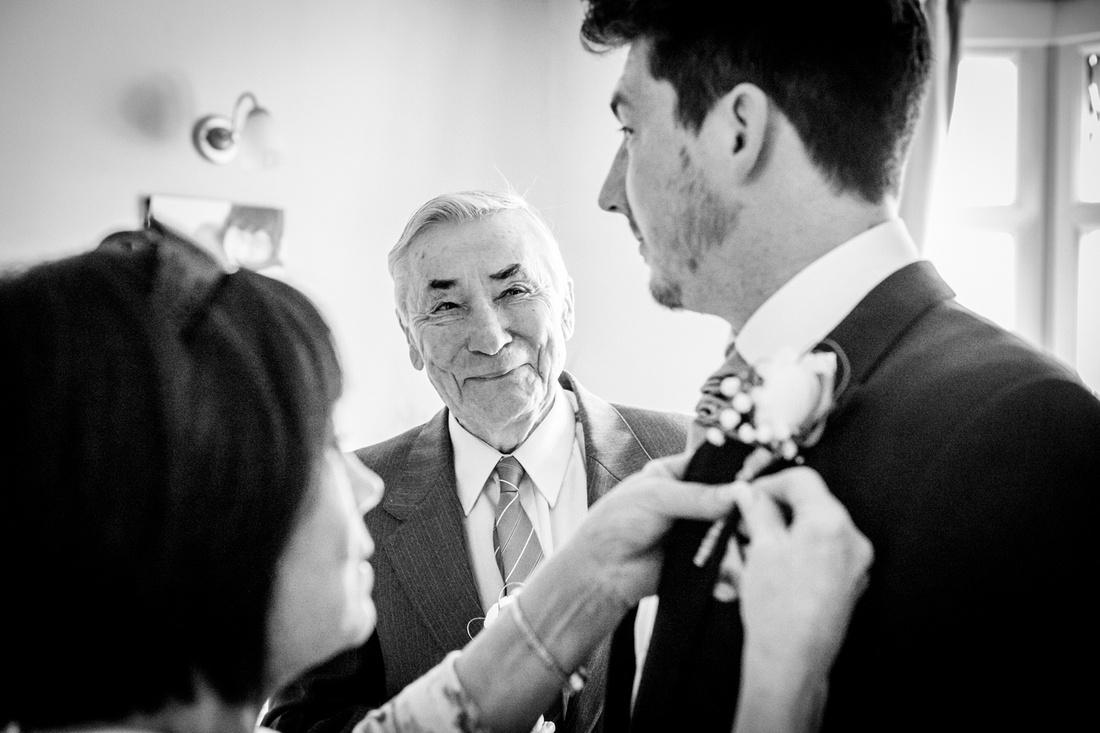 Proud grandad looks at groom getting ready for Ardencote Manor wedding