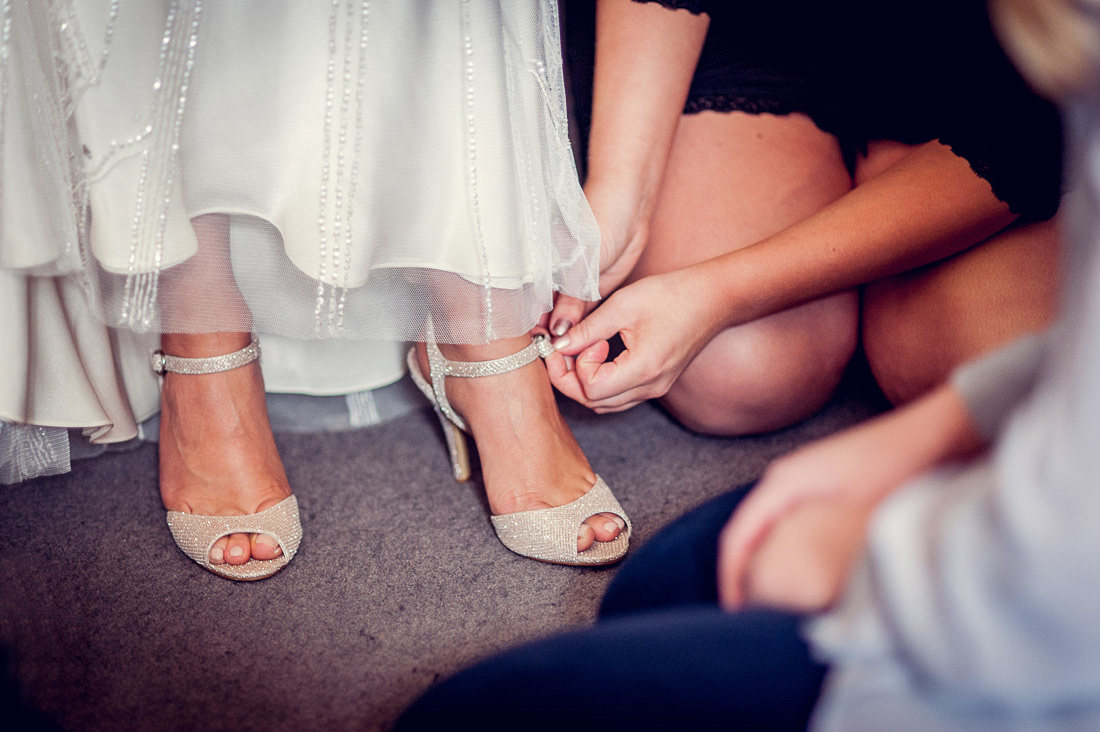 bridesmaid fastening bride's shoes