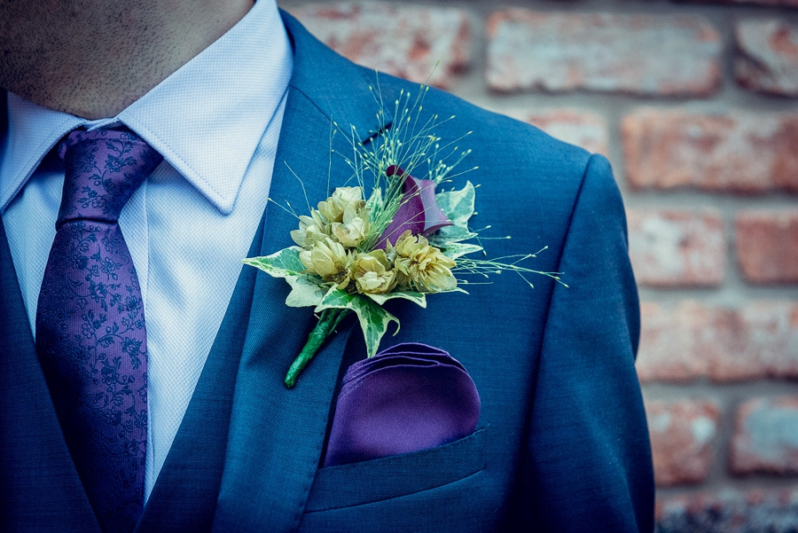 Wedding Photography at Curradine Barns in Worcestershire buttonhole with hops ivy purple flower