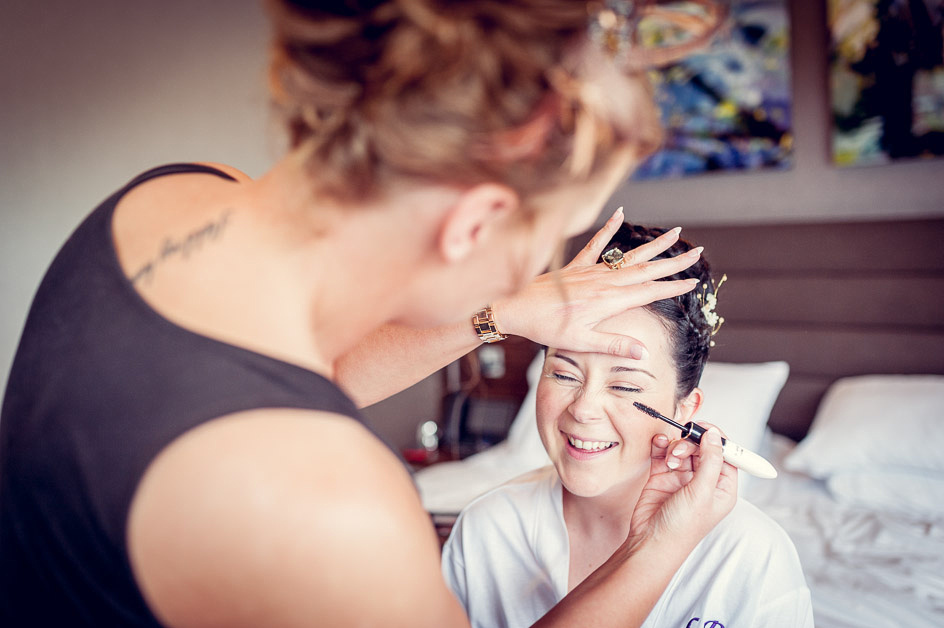 bride laughing while having make up applied