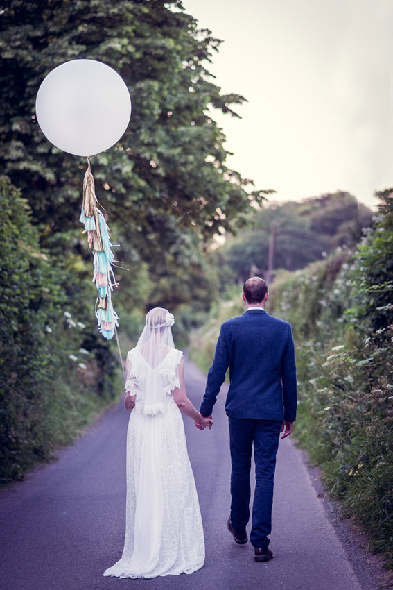 bride and groom walking down country lane with balloon