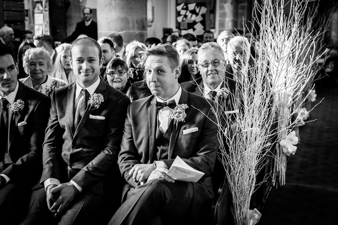 wedding photography at hampton manor groom waiting in Hampton in Arden church