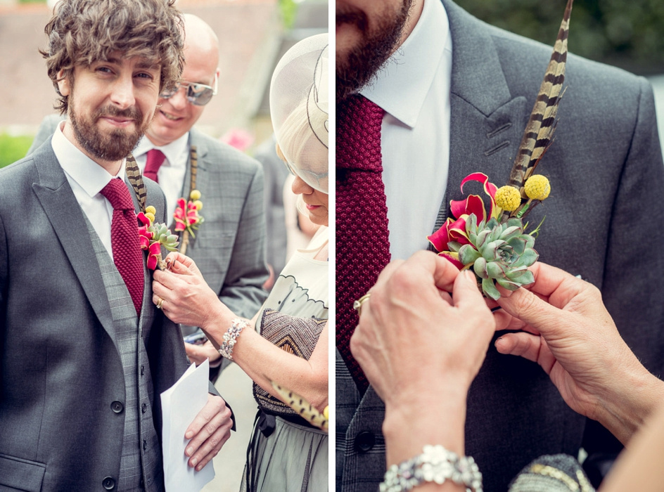 Unusual buttonhole being pinned onto cool groom
