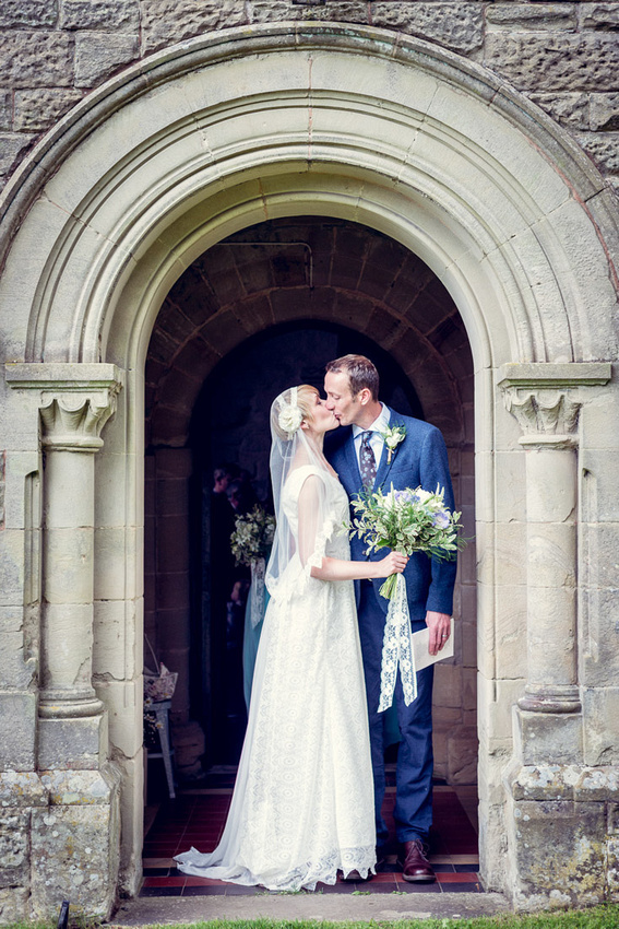 bride and groom kiss in doorway St Mary's Church Hatton Warwickshire
