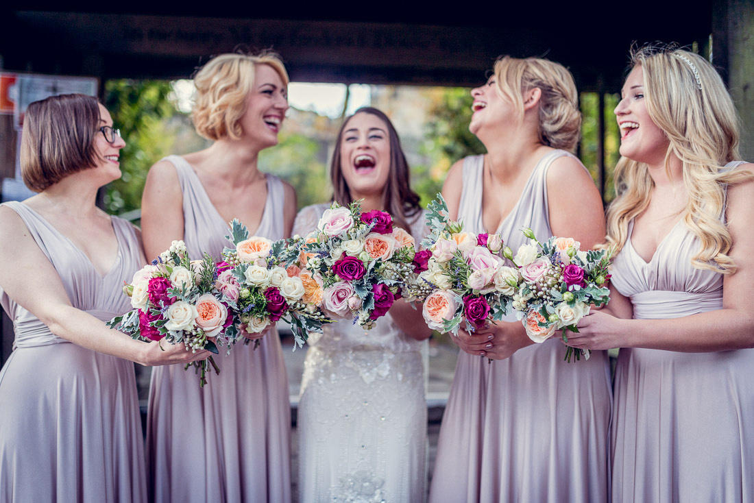 bride and bridesmaids laughing with bouquets outside Hampton in Arden Church