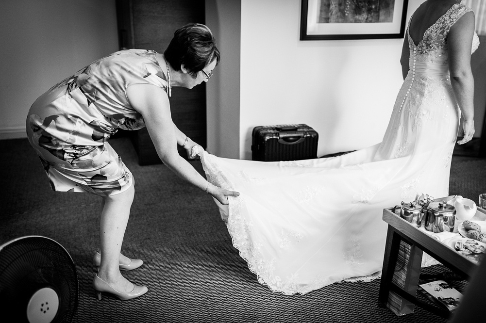 bride's mother adjusting train on wedding dress