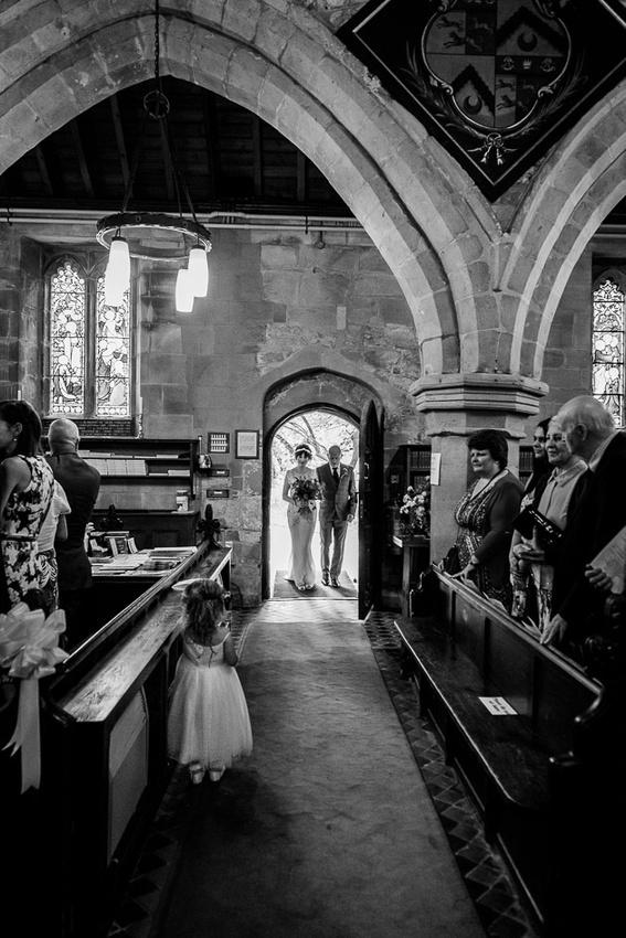 Little bridesmaid watches bride enter St Leonard's Church Beoley