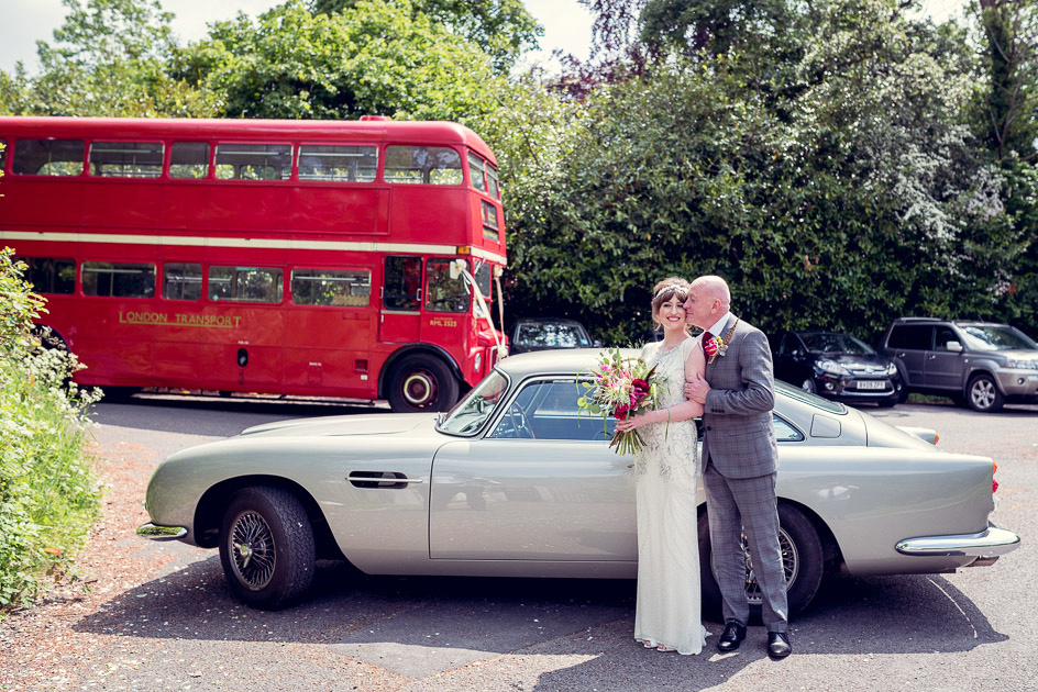 Bride being kissed by dad next to vintage Aston Martin