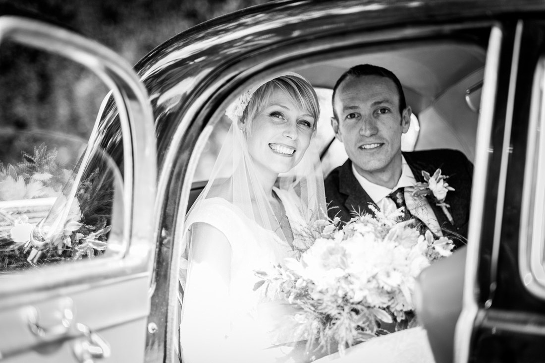 newly married couple in car outside St Mary's Church  Hatton Village Hall wedding