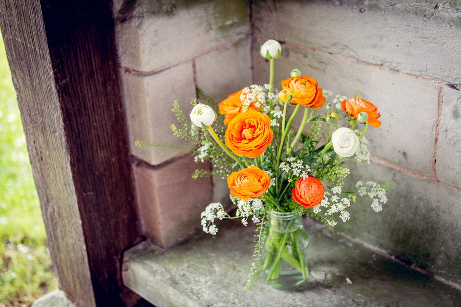 orange ranunculus flowers with cow parsley in vintage milk bottle